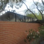 fence on brick wall with lyre design image