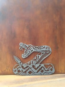 coiled rattle snake about to strike raw steel with a rusted steel background