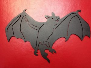 black bat flying powder coated black with red background